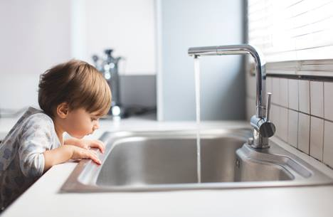 Boy looking down at sink natural gas hot water